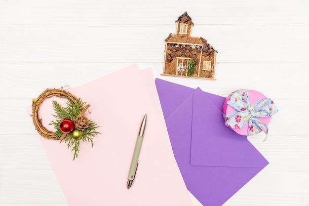 冬の休日の概念をモックアップします。ペンと封筒で白い木製のテーブルに紙の空白のシート