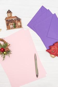 Зимние каникулы макет концепции. чистый лист бумаги на белом деревянном столе с ручкой и конвертами