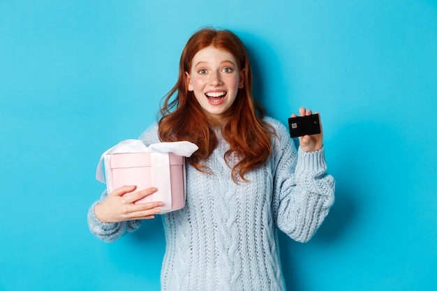 Winter holidays promo offer concept. cheerful redhead woman holding christmas gift and credit card, staring at camera amazed, standing over blue background.
