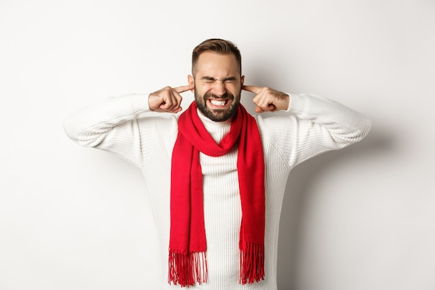 Winter holidays and shopping concept. annoyed man shut his ears with fingers, distressed by loud noise or neighbours, standing against white background