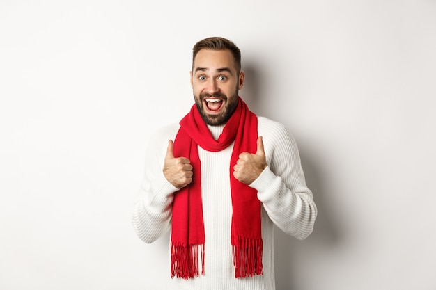 Winter holidays and shopping concept. cheerful bearded man like everything, showing thumbs up in approval, standing amazed against white background