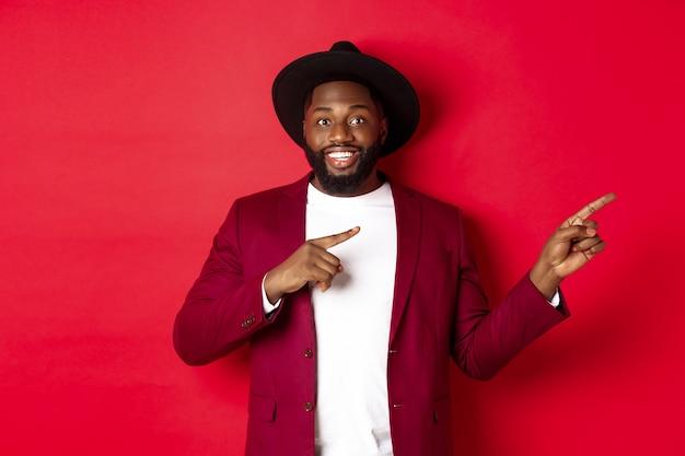 Vacanze invernali e concetto di shopping. elegante uomo afroamericano che punta il dito proprio nello spazio della copia per il logo, in piedi su sfondo rosso
