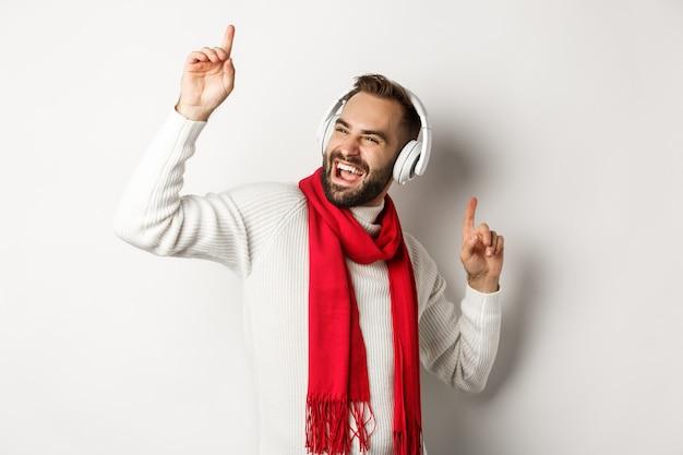 Vacanze invernali e concetto di tecnologia. uomo felice che balla con la musica in cuffia, in piedi su sfondo bianco in maglione