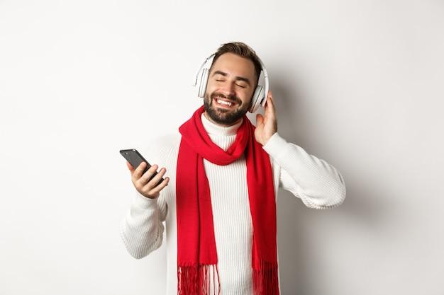 Vacanze invernali e concetto di tecnologia. uomo soddisfatto che ascolta musica in cuffia con gli occhi chiusi, sorride con piacere, tiene in mano smartphone, sfondo bianco.