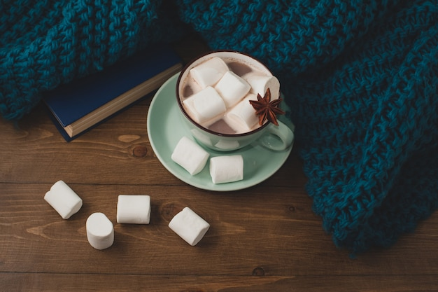 Winter home background - cup of hot cocoa with marshmallow and warm blue knitted sweater on wooden table.