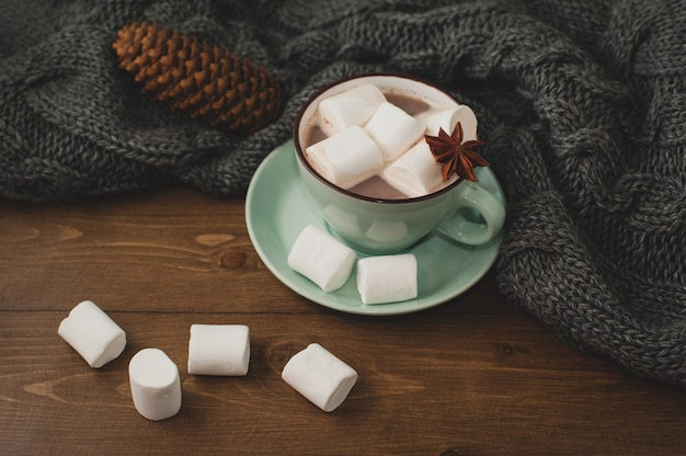 Winter home background - cup of hot cocoa with marshmallow and warm knitted sweater on wooden background.