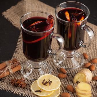 Зимний горизонтальный глинтвейн баннер. очки с горячим красным вином и специями на темном фоне.