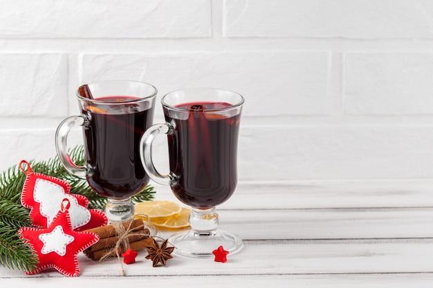 Зимний горизонтальный глинтвейн баннер. бокалы с горячим красным вином и специями, елочные, войлочные украшения
