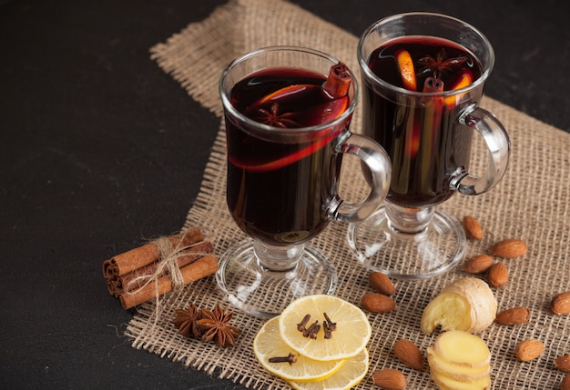 Winter horizontal mulled wine banner. glasses with hot red wine and spices on dark background.