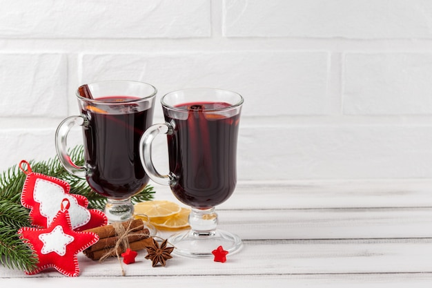 Winter horizontal mulled wine banner. glasses with hot red wine and spices, tree, felt decorations