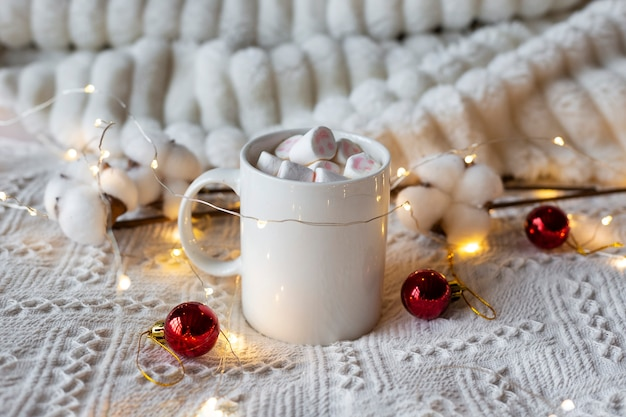 Winter hot chocolate with marshmallows, festive light garland and red christmas tree toys on a white bed