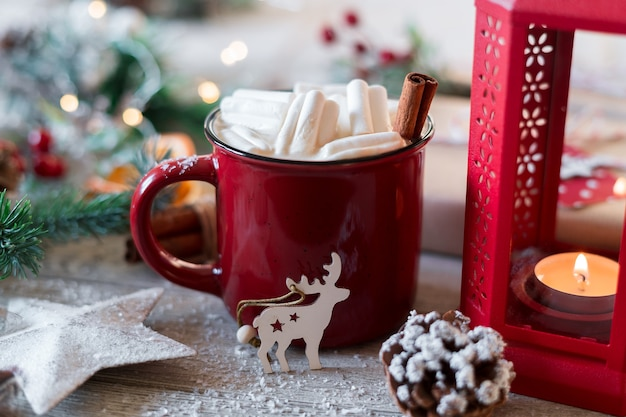 Winter hot drink, cacao with marshmallows and cinnamon or spicy hot chocolate in red cup