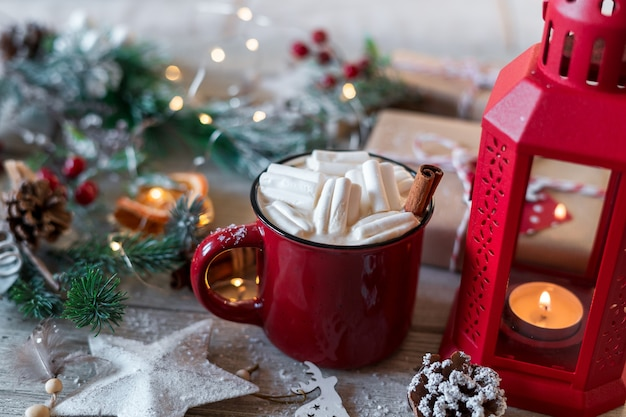 Winter hot drink, cacao with marshmallows and cinnamon or spicy hot chocolate in red cup.