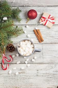 겨울 뜨거운 음료입니다. 크리스마스 장식이 있는 흰색 나무 테이블에 마시멜로를 넣은 크리스마스 핫 초콜릿 또는 코코아
