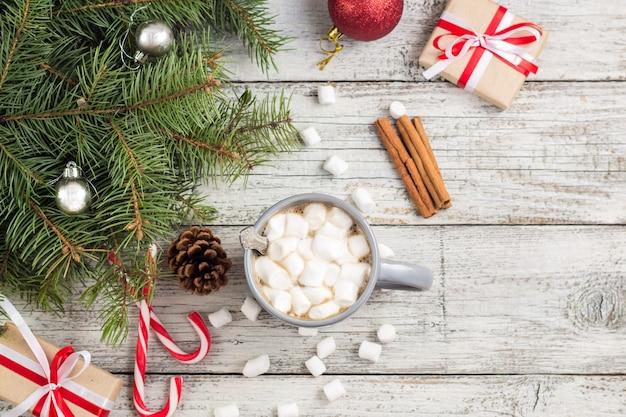 冬の温かい飲み物。クリスマスの装飾が施された白い木製のテーブルにマシュマロとクリスマスのホットチョコレートまたはココア