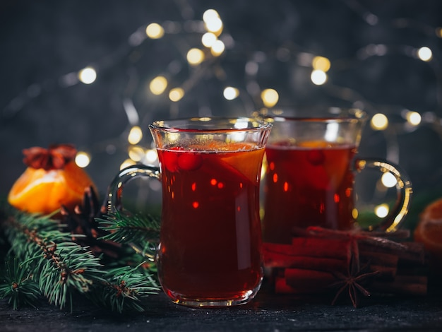 Winter hot drink christmas mulled wine in glasses with anise, cinnamon and tangerine