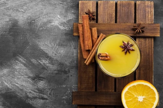 Winter hot drink from oranges and spices on a black surface