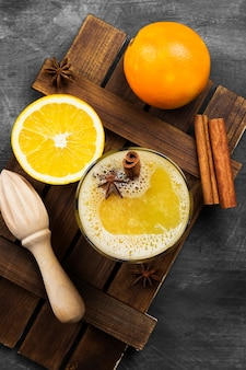 Winter hot drink from oranges and spices on a black surface.