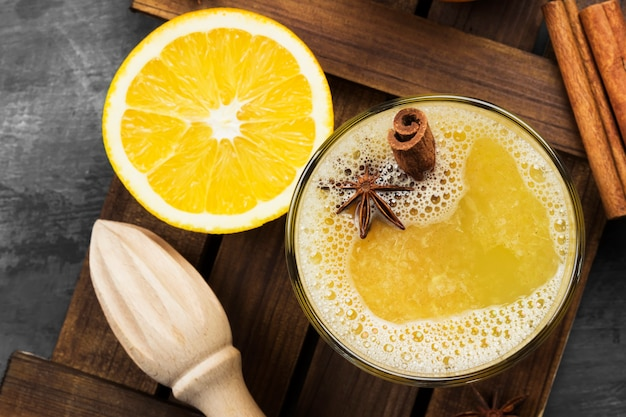 Winter hot drink from oranges and spices on black, top view