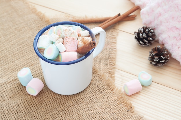 Winter hot drink. hot chocolate or cocoa with pastel colour marshmallow on cozy table