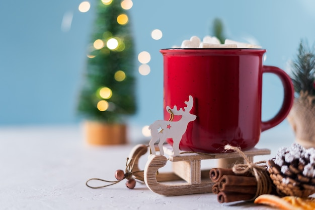 Winter hot drink with marshmallows in red mug and christmas decoration