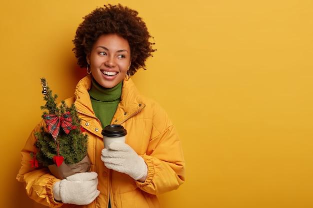 冬、ホットドリンクと人々のコンセプト。幸せな巻き毛の髪の女性は持ち帰り用のコーヒーを飲み、小さな装飾されたモミの木を保持し、クリスマスのお祝いの準備をします