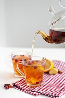 Зимний горячий чай для укрепления иммунной системы. две чашки и стеклянный чайник с чаем, лимоном, имбирем и клюквой на светлом фоне. вид сверху. фото высокого качества