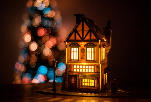 Winter house made of cardboard made with their hands on the table, glow house, decoration for the new year and christmas