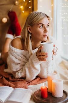 Disposizione hygge invernale con candele accanto alla donna