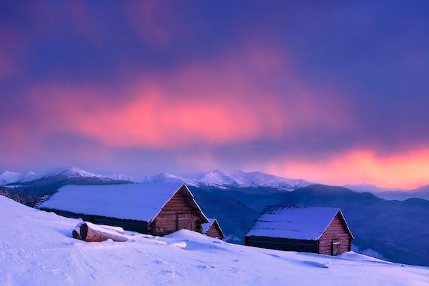 山の村の冬。雪に覆われた古い木造家屋。美しい雲と素晴らしい夕日