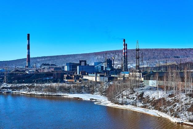川岸の谷に古いコークス化学プラントがある冬の産業景観