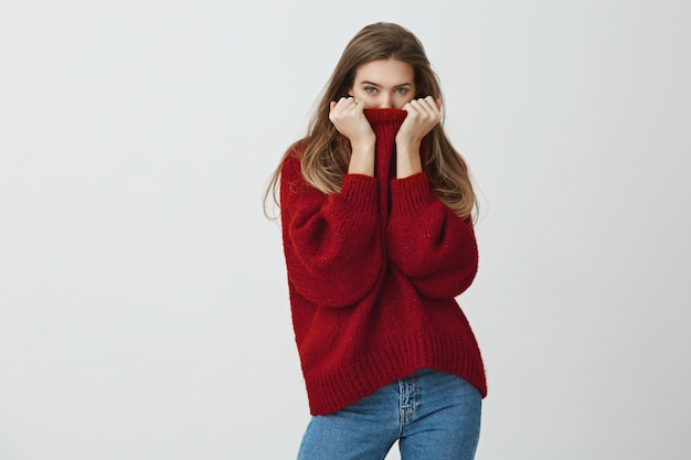 Winter is close. good-looking slender woman in trendy loose sweater hiding face in collar while glancing , feeling cold or blushing of compliments, standing .