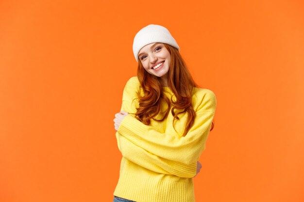 Зима - ее любимое время года. нежная глупая и милая рыжая женщина обнимает себя и наклоняет голову
