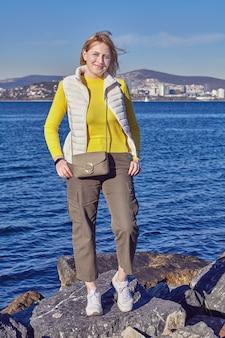Зимний стамбул, побережье острова бююкада в мраморном море, улыбается молодая белая женщина позирует стоя.