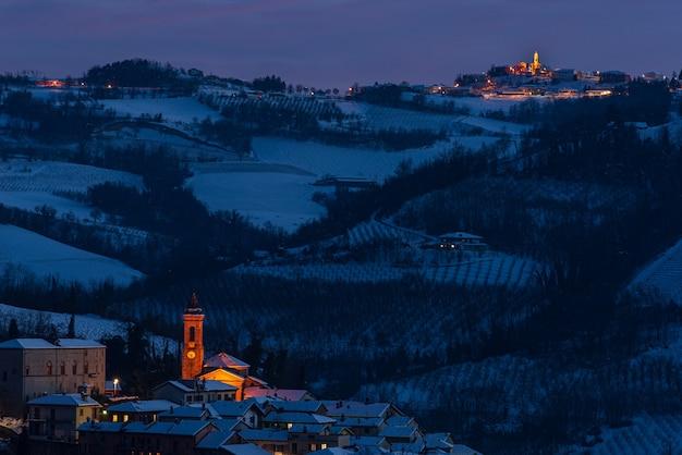 イタリア、ピエモンテ州、ランゲのワイン畑地域の冬の景観。夕暮れの照らされた村、教会、雪の丘の上にある城。