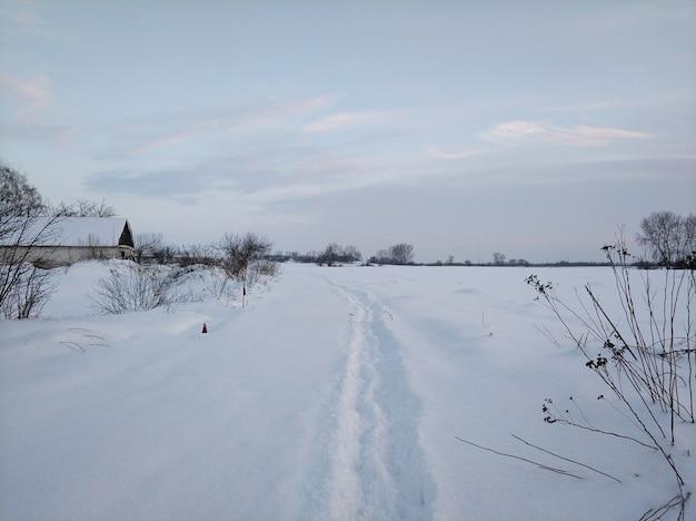 Зимний пейзаж. далекая деревня в холодной части планеты. белая заснеженная дорога.