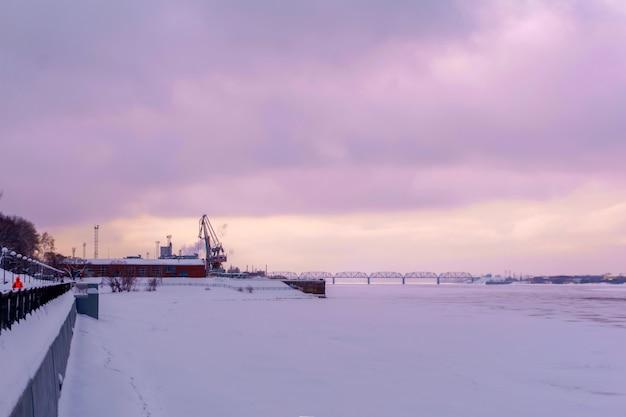 Зимний пейзаж замерзшая река с грузовым портом и набережной на фоне вечернего неба