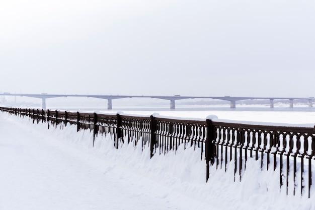 Зимний пейзаж замерзшая река с автомобильным мостом вдали и забором на набережной кастирон