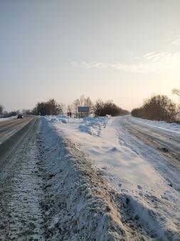 겨울 풍경. 하얀 눈으로 덮여있는 도로. 차가 도로를 따라 운전하고 있습니다.