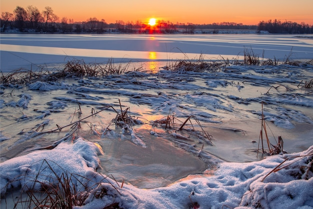 雪に覆われた川岸と前景に雪に覆われた凍った草と太陽を反射する輝く氷のある川の日の出の冬の風景