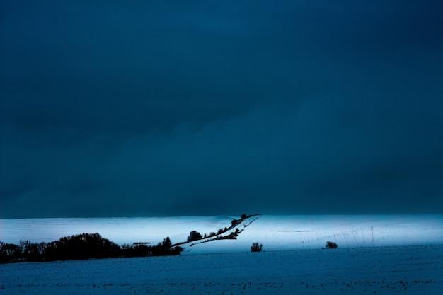 冬の風景、創造性の背景。道路は冬の畑の真ん中にあり、暗い嵐の空_