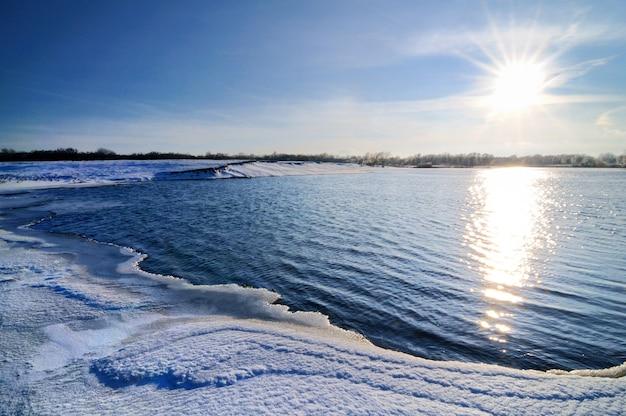 겨울 풍경, 푸른 하늘과 밝은 햇빛, 눈으로 덮인 호수 해안, 나무가 수평선에 자랍니다.