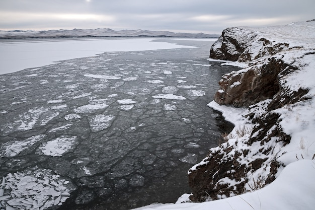 Winter landscape, drifting ice floes surrounded by rocks