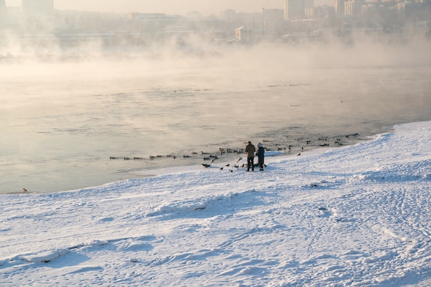 Winter landscape of fogy river in city.