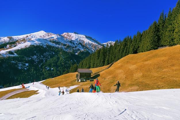 Зимний пейзаж в альпах с зелеными соснами, заснеженными горными вершинами