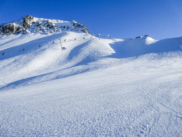 山の冬の風景です。山は晴れた冬の日に雪で覆われています
