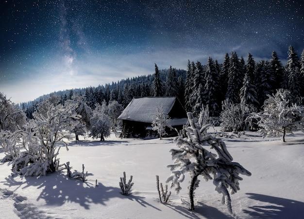 Зимний пейзаж горное село в украинских карпатах. яркое ночное небо со звездами, туманностью и галактикой. астрофото глубокого неба