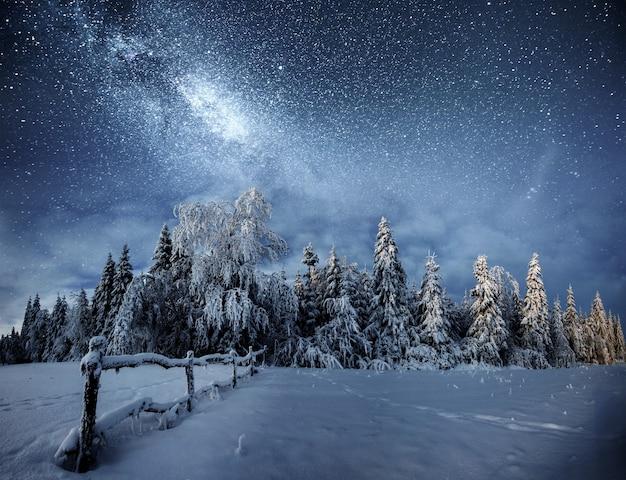 Зимний пейзаж. горное село в украинских карпатах. яркое ночное небо со звездами, туманностями и галактиками. астрофотография глубокого неба.