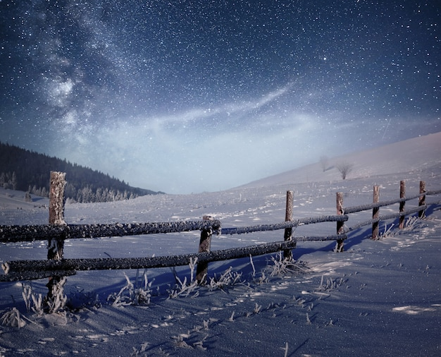 Winter landscape. mountain village in the ukrainian carpathians. vibrant night sky with stars and nebula and galaxy. deep sky astrophoto