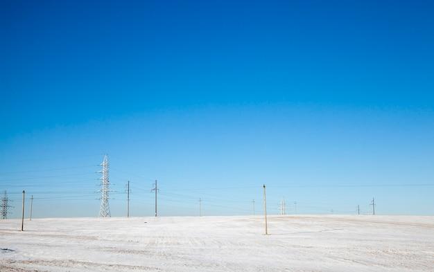 흰 눈으로 덮인 들판의 겨울 풍경, 들판에는 전선이 달린 많은 수의 전주가 있습니다.